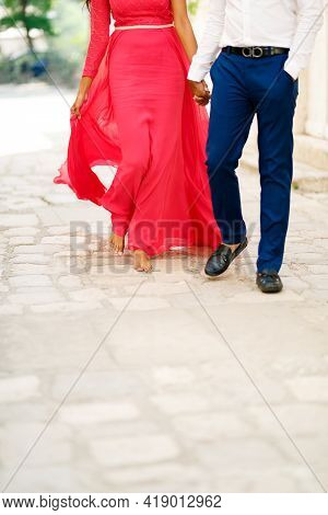 Barefoot Bride In A Long Bright Pink Dress And The Groom Walking Along A Cobbled Road And Tenderly H