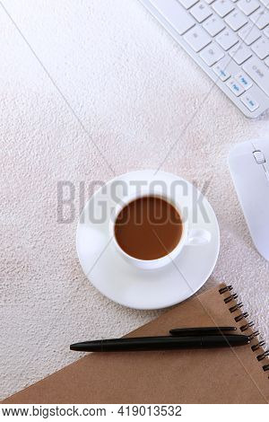 A Cup Of Coffee On The Desktop.computer And Notepad For Writing On A Light Background. Keyboard For