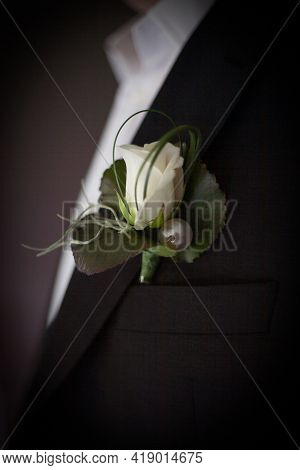 The Groom In A Suit Straightens His Tie. Buttonhole On The Lapel Of The Jacket. Young Man In A Busin
