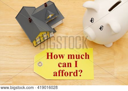 How Much Can I Afford Message On A Gift Tag With A Model House With A Piggy Bank On Wood Desk
