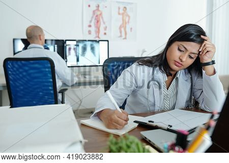 Tired Indian Female Cardiologist Describing Cardiogram Of Patient And Taking Notes In Document