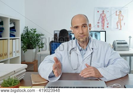 Portrait Of Physician In Labcoat And Earphones Having Online Meeting Or Conference With Colleagues