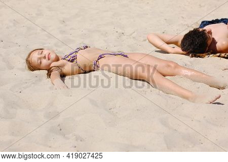 Young Girl And Boy Are Lying On The Sand And Sunbathing. They Like To Sunbathe And Swim In The Sea