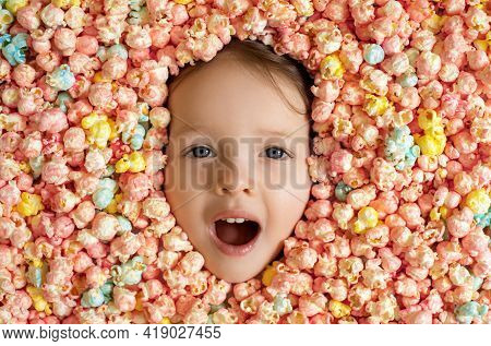 The Baby's Face Is Surrounded By A Large Amount Of Colorful Sweet Popcorn. The Girl's Mouth Dropped