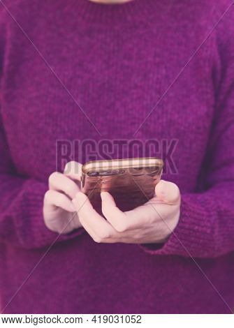 Midsection Of A Girl Wearing Berry Colour Sweater And Holding Her Smartphone Whilst Texting With Cop