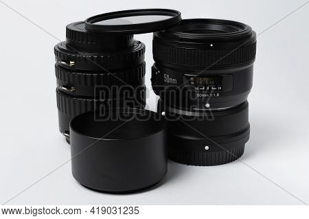 The Lens With The Macro Rings And The Lens Hood Are Positioned Vertically In The Photo And Are Isola