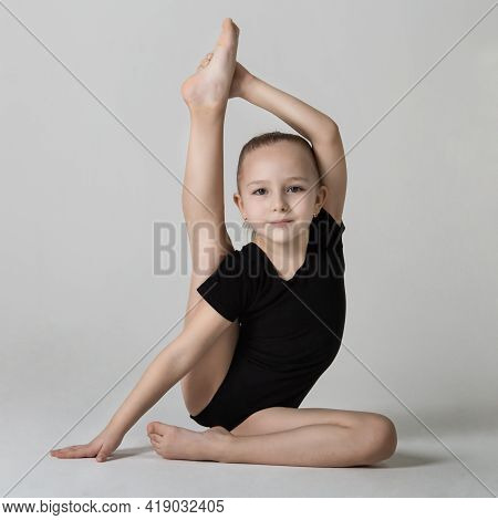 Little Gymnast Demonstrates Flexibility And Balance In A Gymnastic Pose