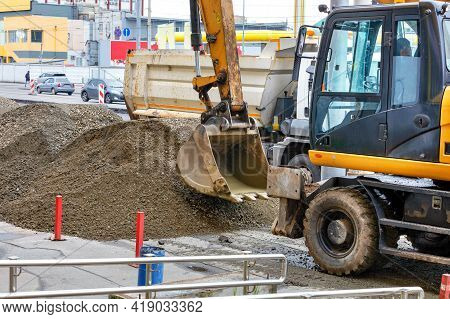 A Road Excavator Bucket Works On A Sidewalk Fenced With Red Posts And Loads Rubble And Sand Into The