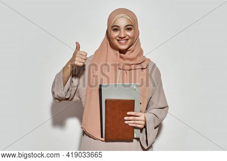 Happy Young Arabian Woman Student In Hijab With Notepad Smiling At Camera And Showing Thumb Up While