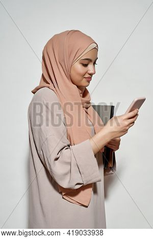 Happy Young Arabian Girl Student In Hijab Using Smartphone While Posing Sideways On Light Background