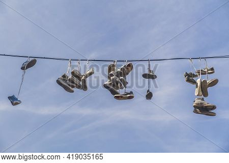 Old Worn-out Shoes Hang From Wires In Slovenia