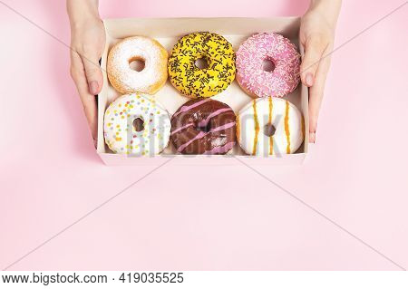 Female Hands Hold A Box With Glazed Donuts On A Pastel Pink Background. Concept Confectionery Store,
