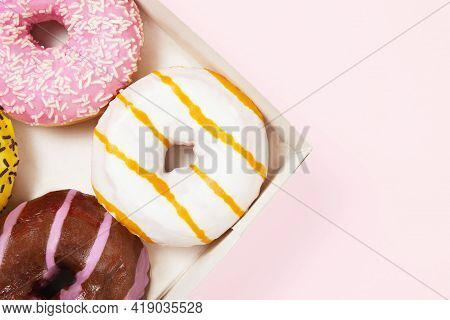 Closeup Round Colored Donuts With Sprinkles And Topping. Glazed Doughnut Box. Pastel Pink Background