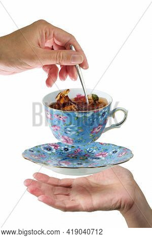 Female Hand With Spoon Mixing A Tea In A  Blue Porcelain Levitating Teacup, Isolated White Backgroun