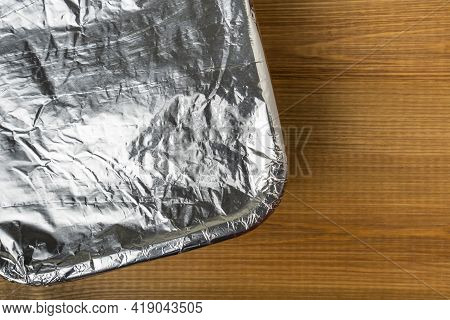 Tray With Meal Wrapped In Aluminum Foil For Baking In The Oven. Aluminum Foil Texture Close Up.