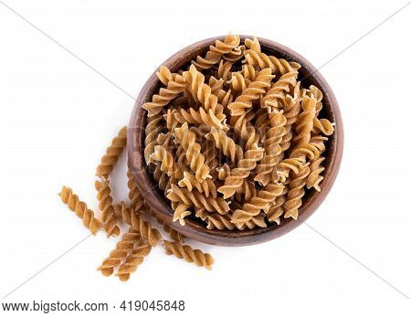 Whole  Grain Fusilli In Wooden Bowl Isolated On White