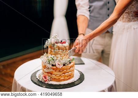 Bride And Groom Cut Together A Two-tiered Wedding Cake Decorated With Flowers And Berries At A Weddi