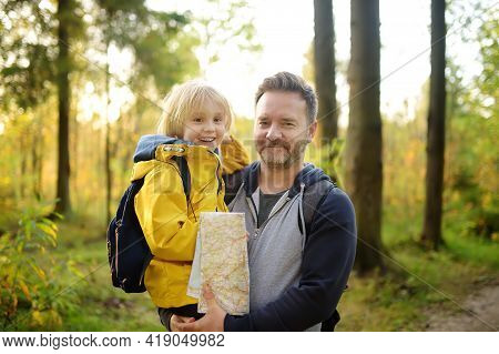 Schoolchild And His Mature Father Hiking Together And Exploring Nature. Boy With Dad Spend Quality F