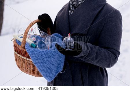 A Woman In A Gray Coat Holds A Basket Of Hijama Cans. Hijama Jars And Hijama Pump, Bloodletting, Chi