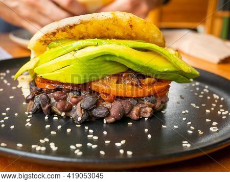 Typical Venezuelan Snack Arepa Stuffed With Black Beans With Smoked Dried Tomato And Avocado Served