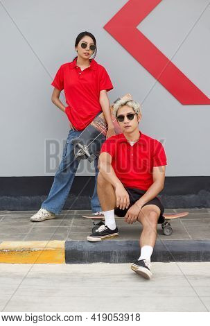 Asian Couple Resting After Skateboarding. A Young Woman In A Red T-shirt With Collar Holding The Sur