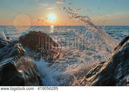 Sea Waves Crushing Over The Big Rocks With Beautiful Sunset Sky Background