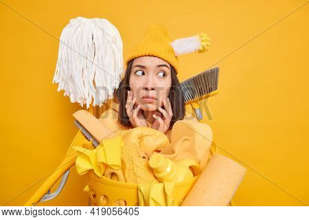 Surprised Asian Female Maid Keeps Hands On Face Looks Away Uses Different Cleaning Tools To Bring Ho