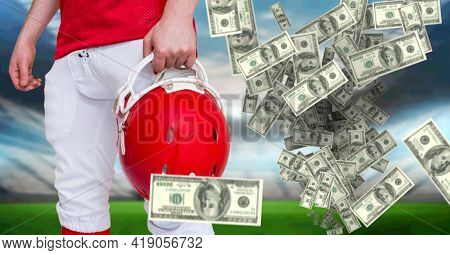 Composition of american dollar bills over midsection of american football player in sports stadium. victory, business, sports and competition concept digitally generated image.