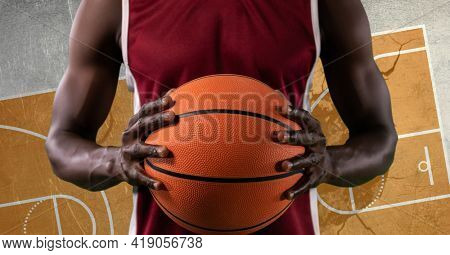 Composition of basketball player holding basketball over basketball court cracked distressed surface. sports and competition concept digitally generated image.