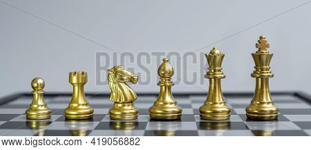 Gold Chess Figure Team (king, Queen, Bishop, Knight, Rook And Pawn) On Chessboard Against Opponent D