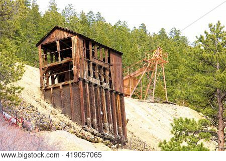 Vintage Wooden Mining Mill On A Mountainous Slope Surrounded By An Alpine Coniferous Forest At The G