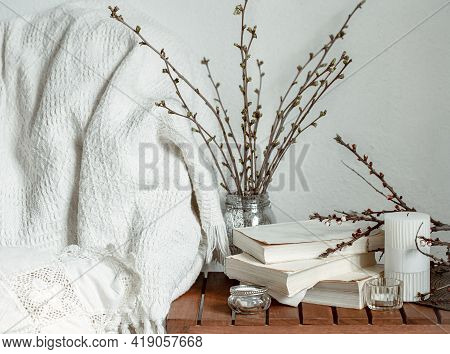 Composition With Spring Branches, Books And Candles In The Home Interior Of The Room.