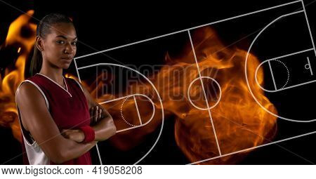 Composition of female basketball player over basketball court and flames. sport and competition concept digitally generated image.