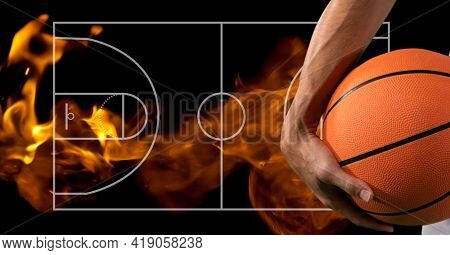 Composition of midsection of basketball player holding basketball over basketball court and flames. sport and competition concept digitally generated image.