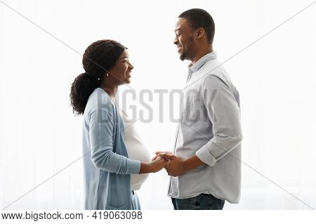 Sensual Pregnant Black Couple Cuddling While Spending Time At Home