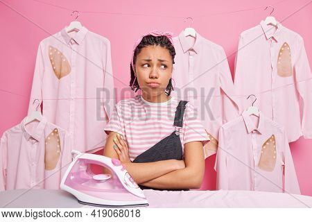 Displeased Laundry Worker Works In Wash House Looks With Sad Frustrated Expression Keeps Arms Folded