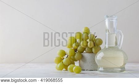 Organic Vegetable Oil From Grape Seeds In A Glass Bottle With Green Grapes.