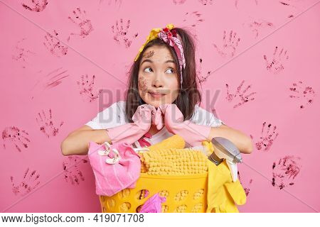 Thoughtful Young Asian Woman Leans At Laundry Basket Concentrated Above Has Dirty Look Wears Protect