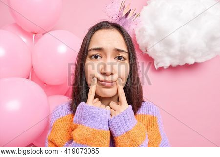 Sad Dejected Asian Woman Has Dark Hair Makes Smile With Fingers Being In Bad Mood On Birthday Party