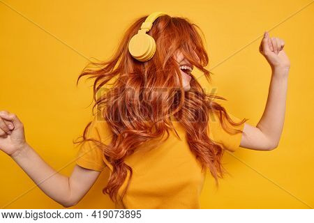 Cool Millennial Girl Keeps Arms Raised Dances Carefree Enjoys Every Bit Of Music Wears Wireless Head