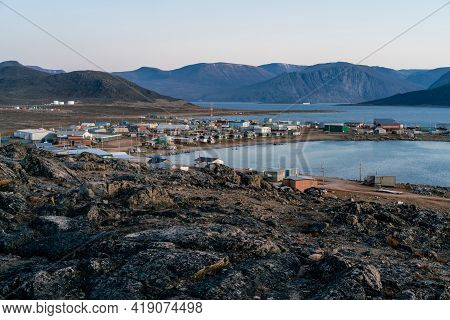 Dusk In A Harsh Arctic Landscape With Bare Hills And Ocean. Overlook Of Inuit Settlement Of Qikiqtar