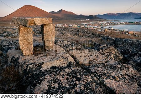 Dusk In A Harsh Arctic Landscape With Bare Hills And Ocean. Inuksuk With Inuit Settlement Of Qikiqta