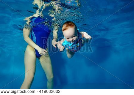 An Infant Dives And Swims Underwater In A Childrens Pool With Its Eyes Open. Mom-coach Insures Her I