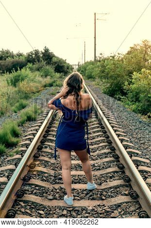 Beautiful Attractive Woman With Long Hair In Blue Dress On The Old Railroad. Backview Image.