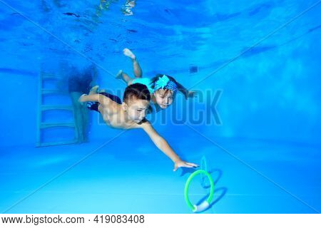 The Children, A Happy Girl And Boy, Dive Together To The Bottom Of The Pool And Collect Toys Underwa
