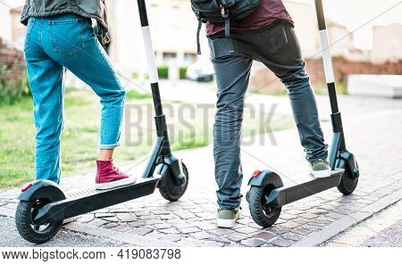 Close Up Of City Commuters Using Electric Scooter At Urban Park - Millenial Students Riding New Mode