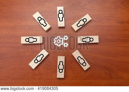 A Circle Of Figures Of People Surround Gears. Teamwork To Joint Efforts To Solve Problems.  Brainsto