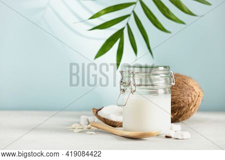 Coconut oil in jar with fresh coconut and tropical leaves on blue background, Spa cosmetic and food ingredient, space for text