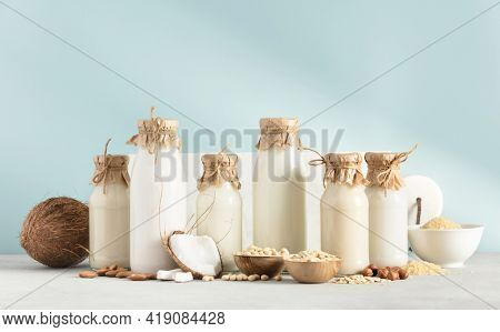 Vegan non dairy plant based milk in bottles and ingredients on blue background. Alternative lactose free milk substitute
