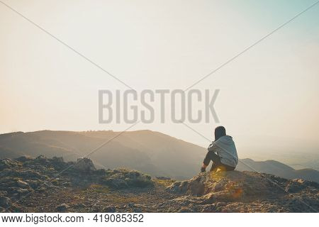 Female Person Sit Alone And Looks Around On The Edge Of The Cliff With Sunny Sky Background. Concept